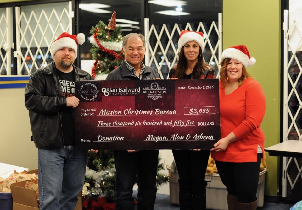 Four people behind a huge printed check